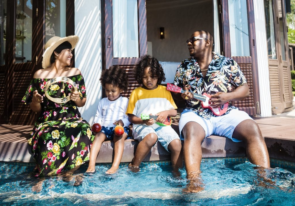 family of four sitting at hotel poolside playing in water