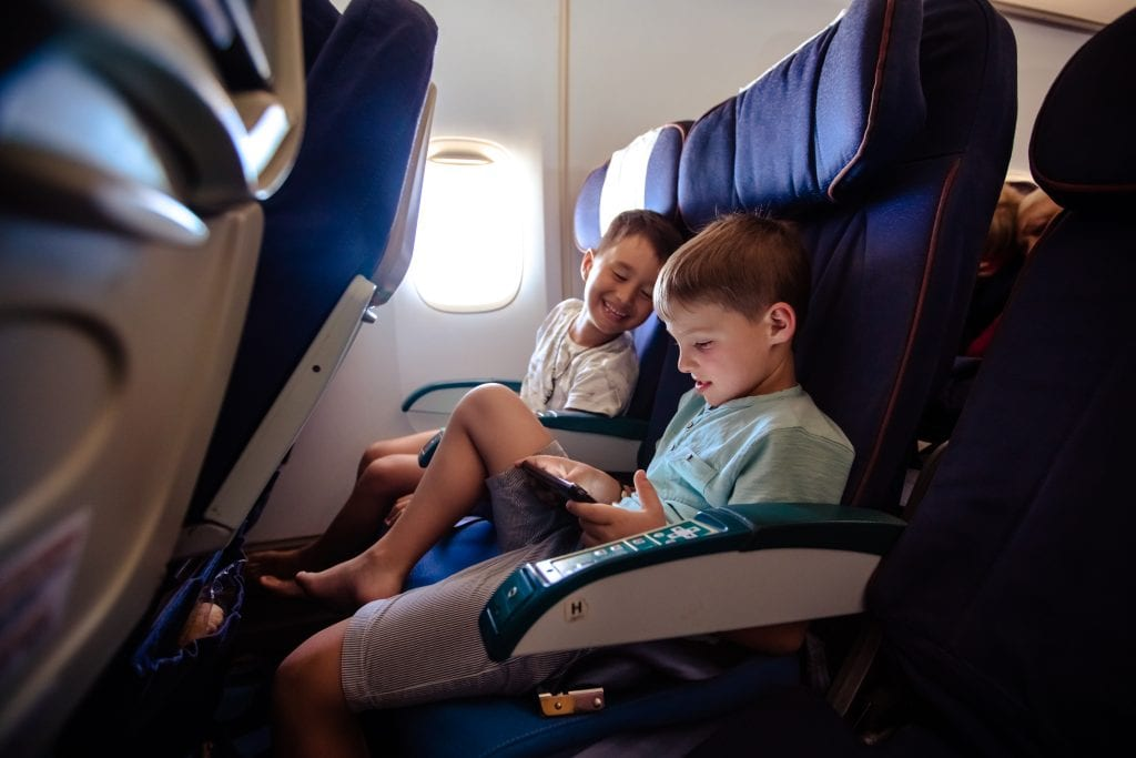 Two boys sitting in airplane seats on a sensory friendly airline