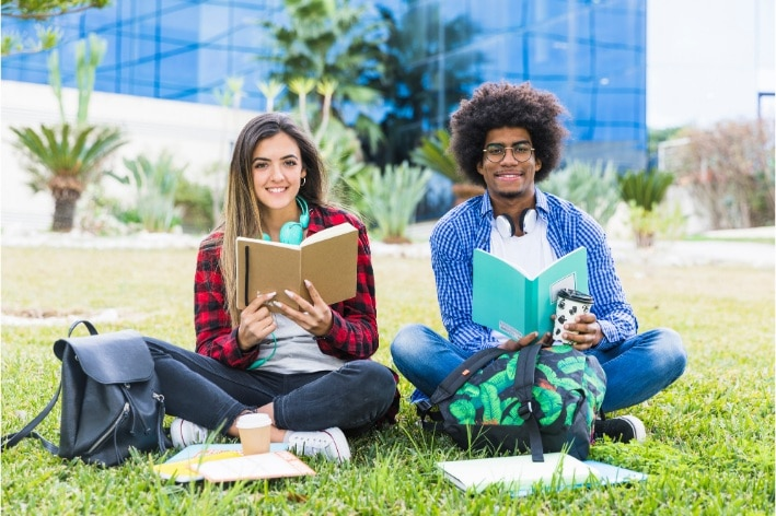 Diverse young couple holding books sitting lawn sensory friendly university campus.