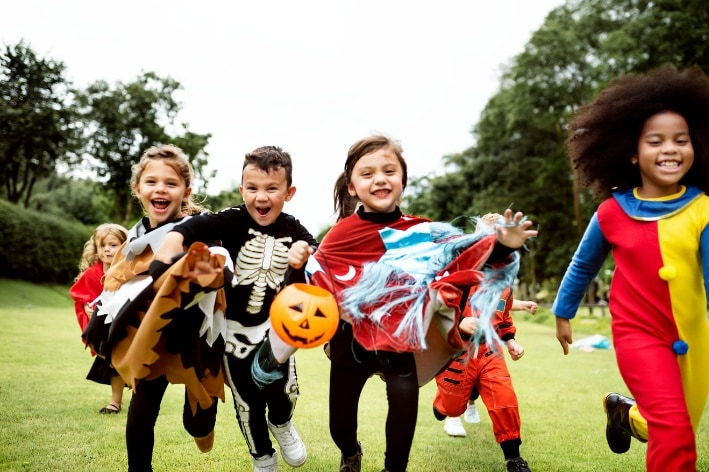Diverse group of children wearing Halloween costumes.