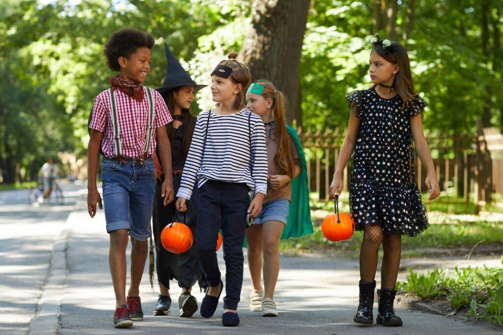 Group of children walking dressed in Halloween costumes.