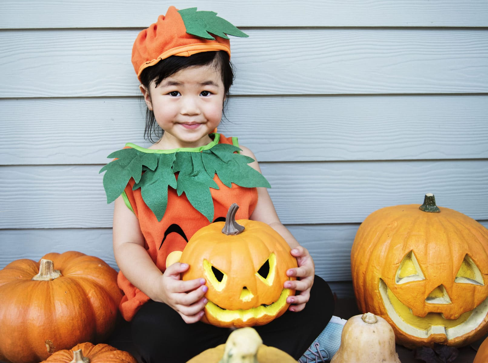 Young girl in pumpkin costume sitting with pumpkins for Halloween.