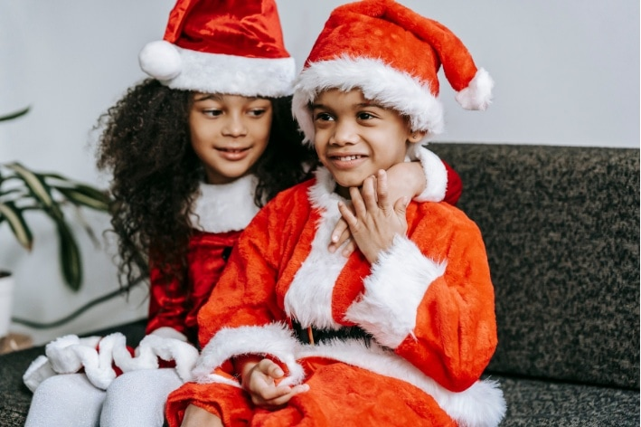 Siblings dressed up as Santa for Christmas smiling at camera