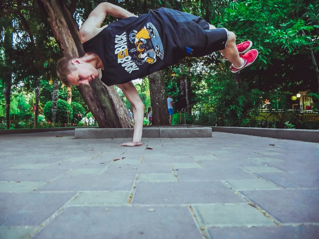 Young man breakdancing balancing on one hand.