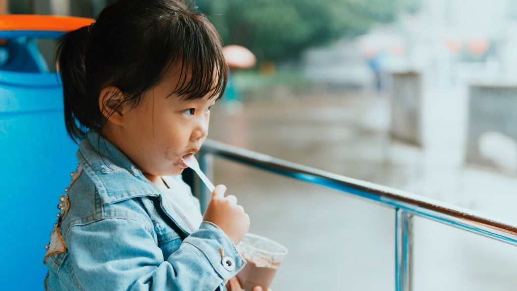 Young Asian girl eating ice cream.