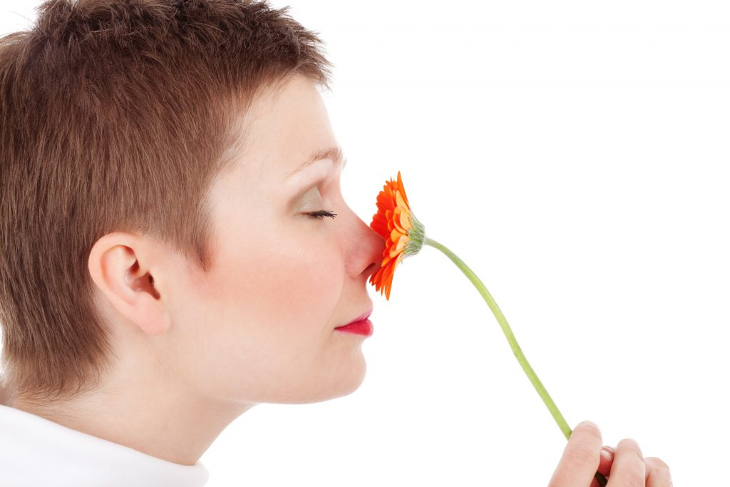 Woman smelling flower.