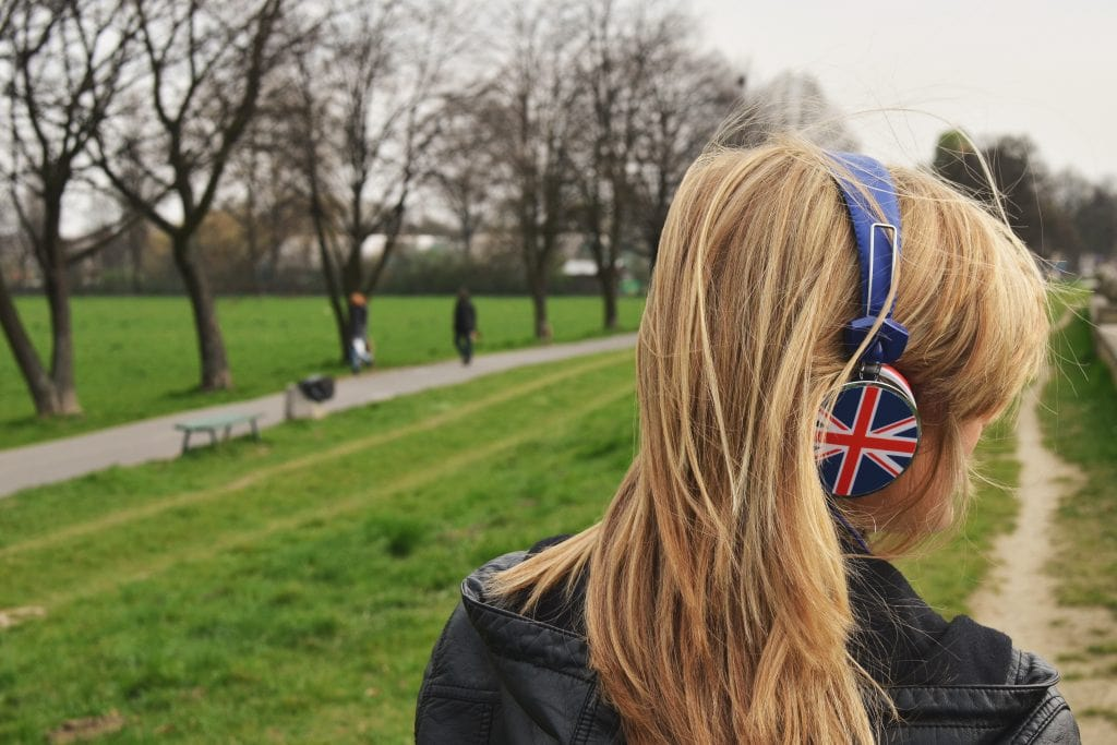 Girl wearing headphones standing in park.