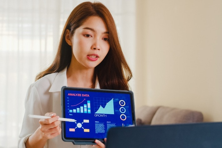 Asian woman presenting information on tablet.