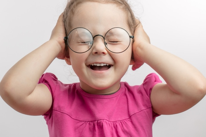 Young girl wearing glasses covering her ears.