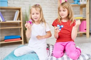 Two young girls playing with fidget sensory friendly toys.