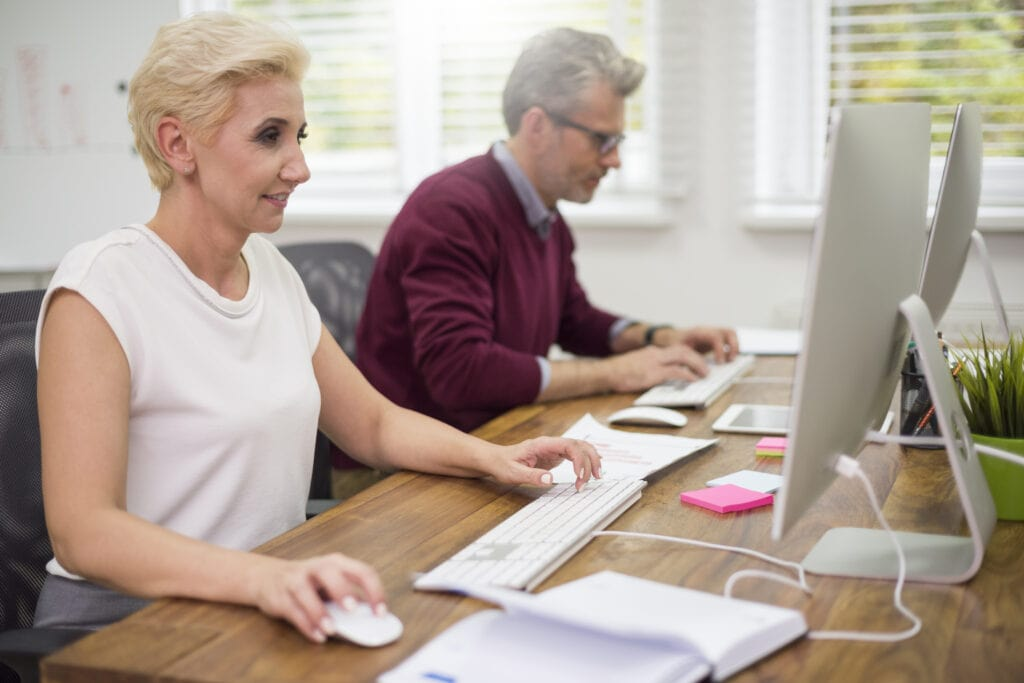 Man and woman co-workers sitting at desk in sensory friendly office.