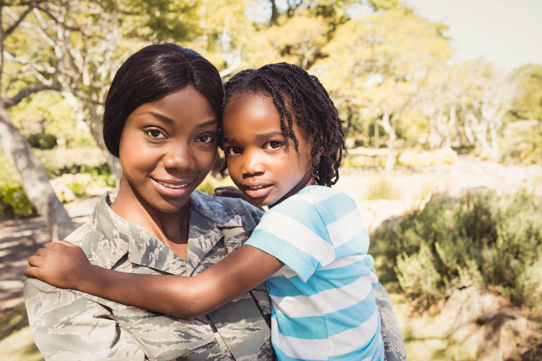 African American woman in military uniform standing and holding young child.