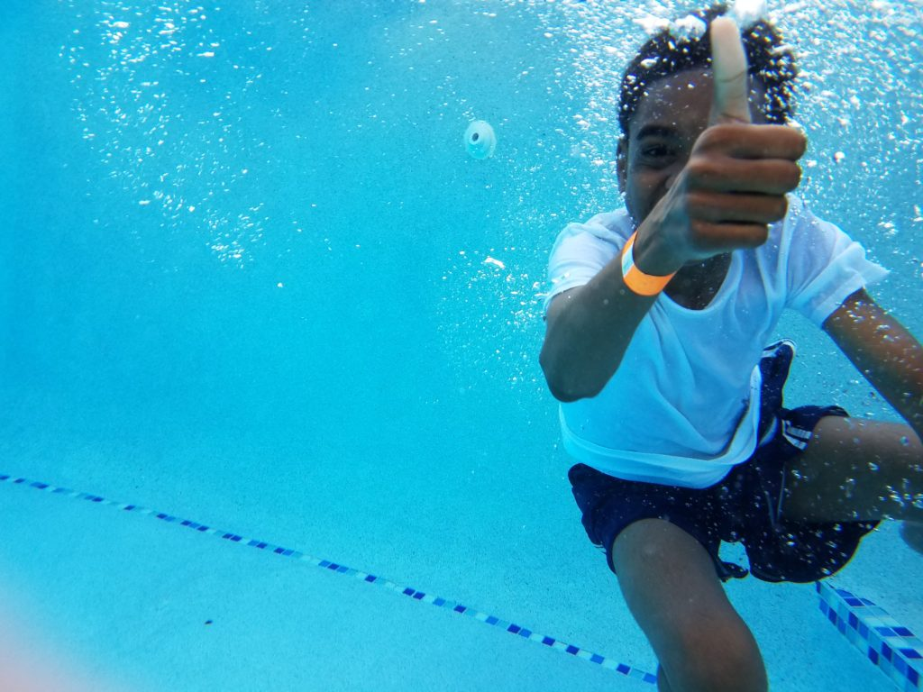Child swimming underwater giving a thumbs up.