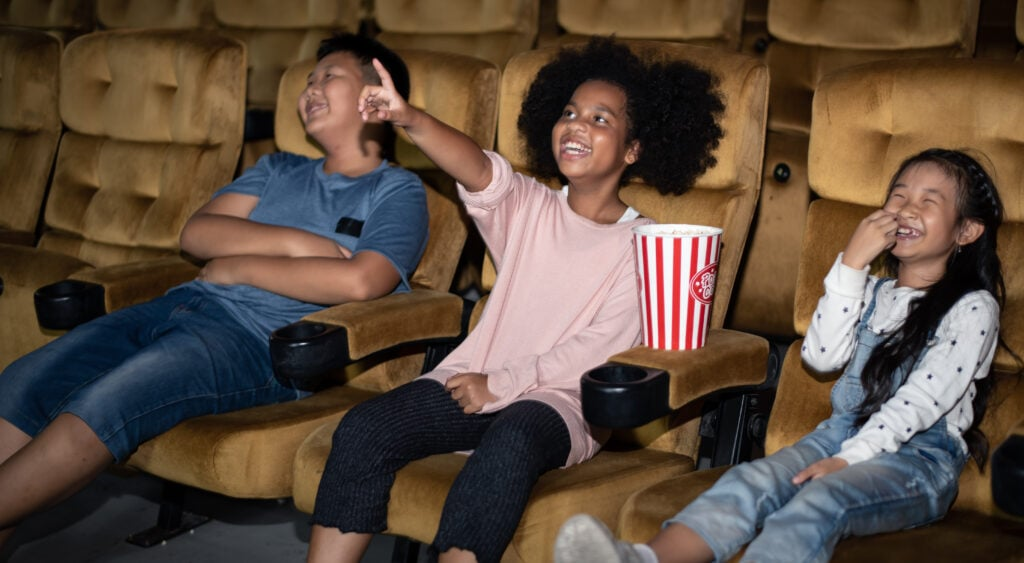 Three kids watching a movie in a sensory-friendly cinema.