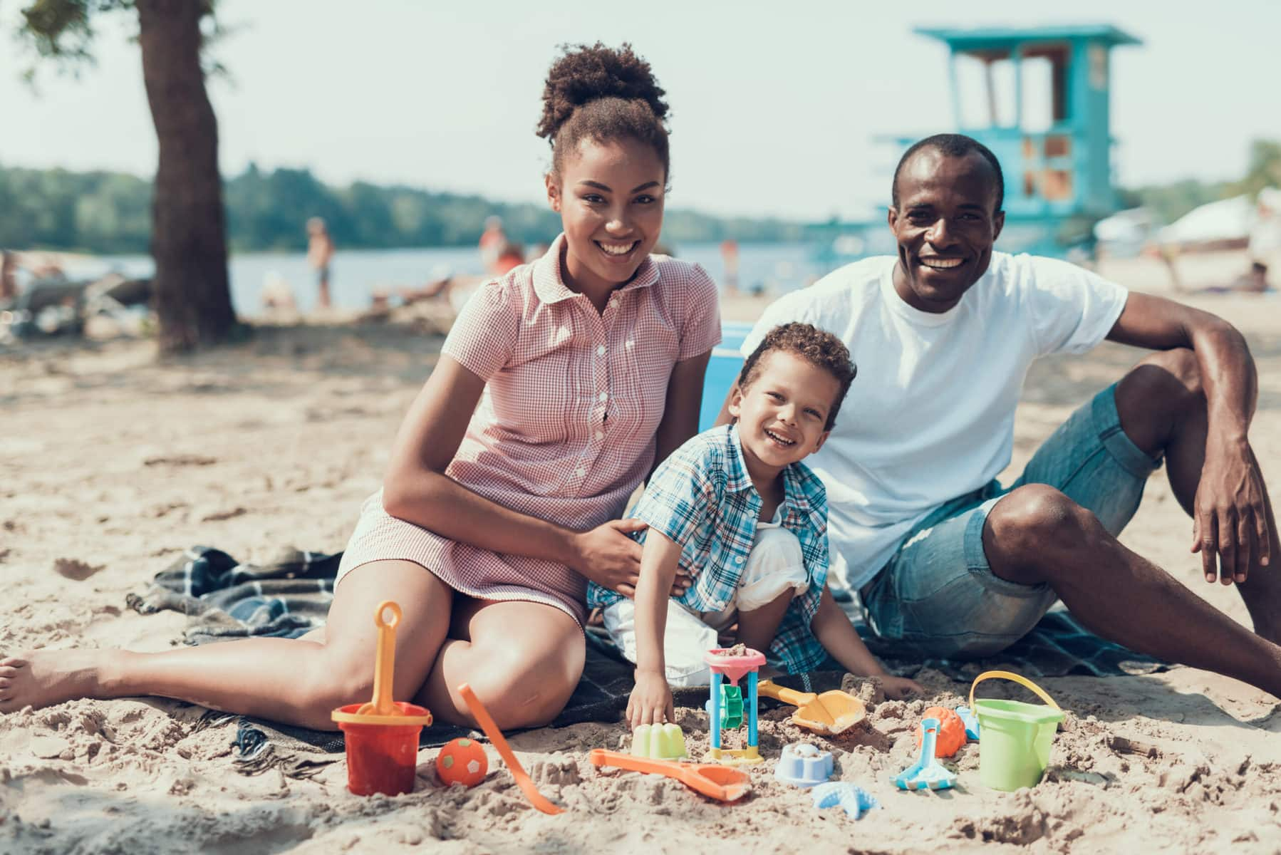 Mother, father and son sitting at beach, a family travelling with autism looking for sensory-friendly experiences.