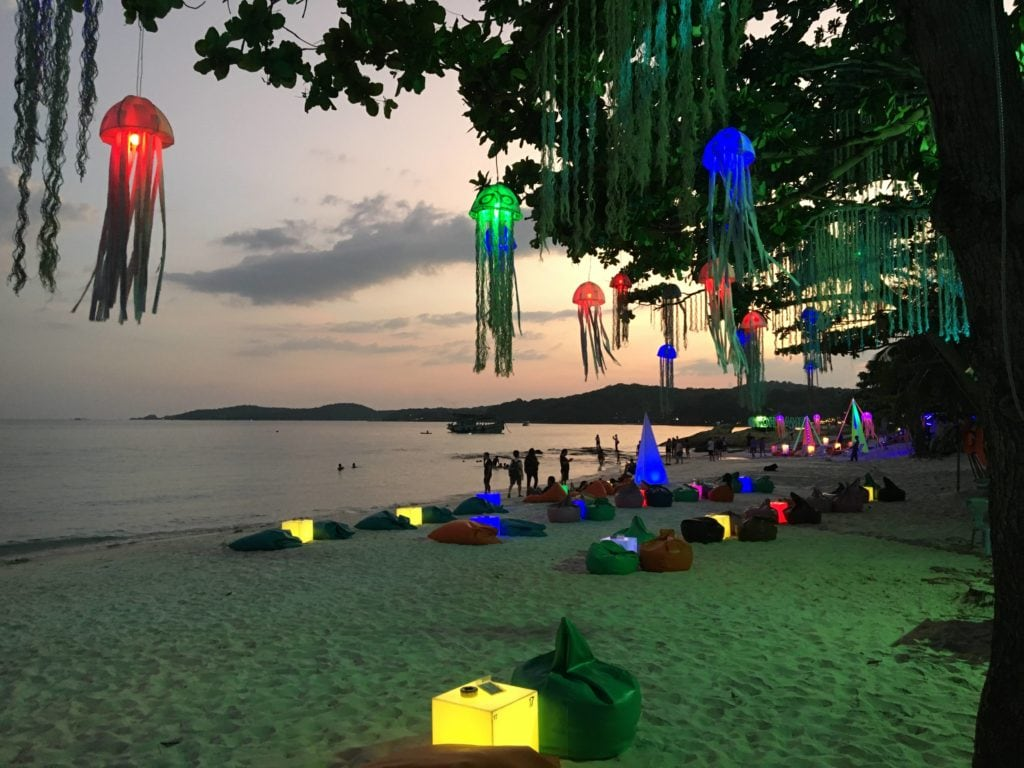Sensory friendly beach with lights hung up in tree.