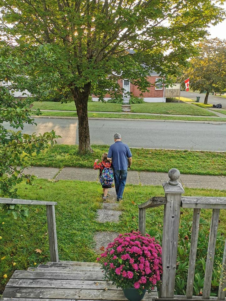 Young boy and day walking down path away from house