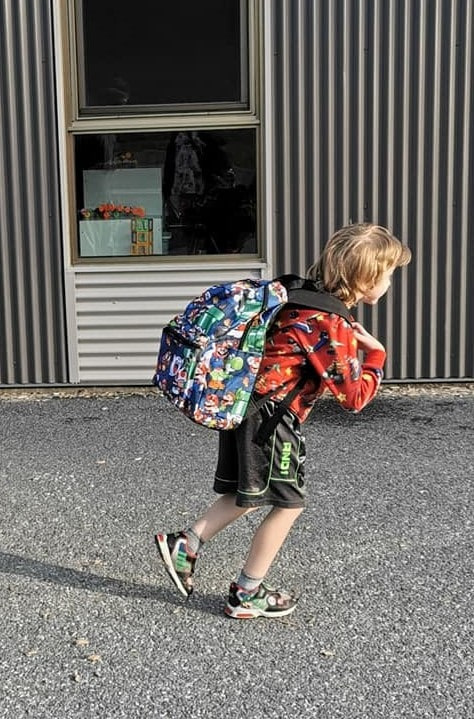 Young boy with backpack going to school