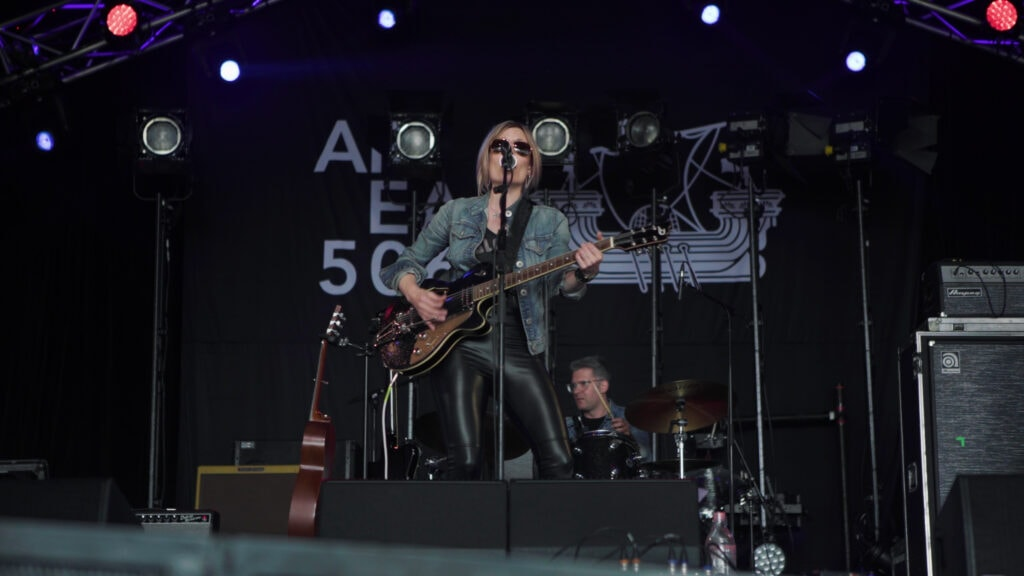 Christina Martin playing guitar and singing on stage.