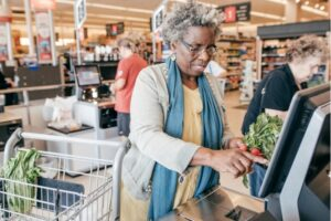 Senior woman checking out her groceries.