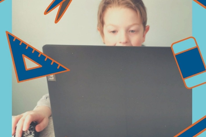 Child sitting at desk in front of computer.