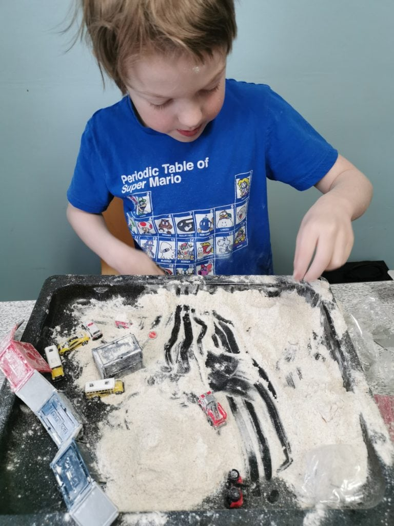 Young boy engaging in a sensory friendly flour activity.