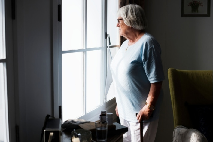 Older woman holding cane looking outside her window feeling social isolation