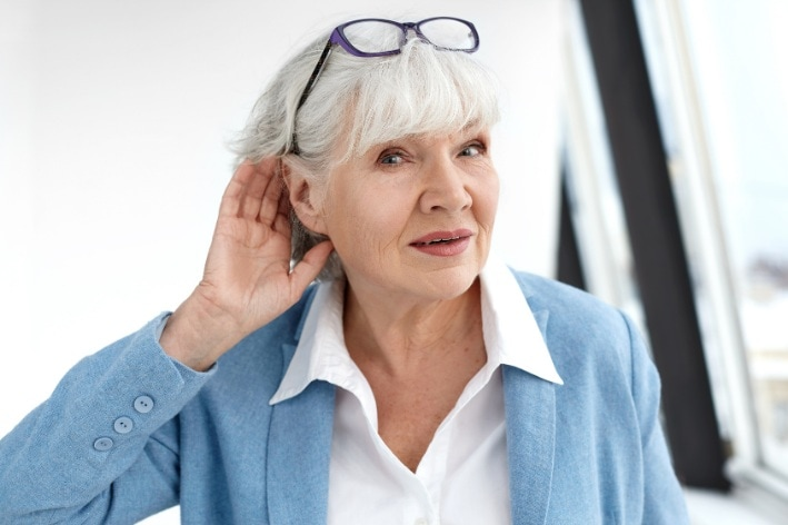 Older woman cupping her ear.
