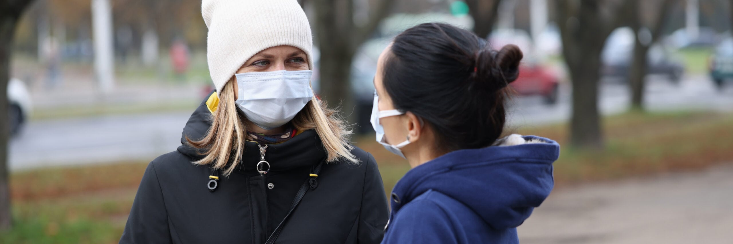 Two young women communicating in protective face masks outside