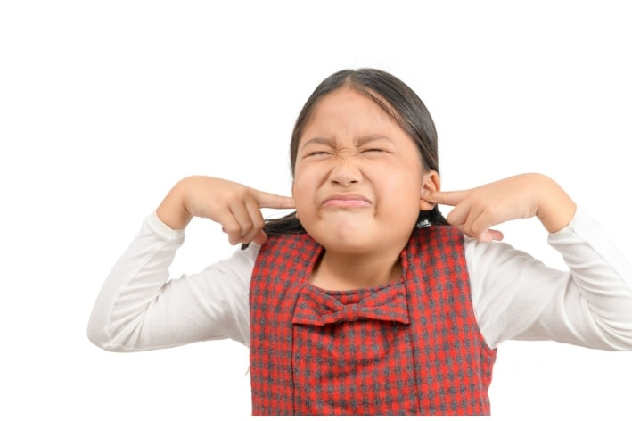 Young Asian girl plugging her ears.