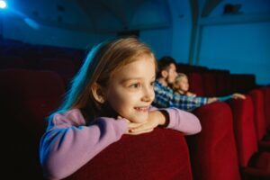 Young girl sitting in movie theatre leaning on chair.
