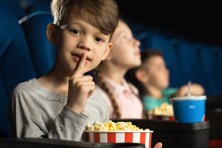 Young boy sitting in movie theatre with with his finger over his mouth.