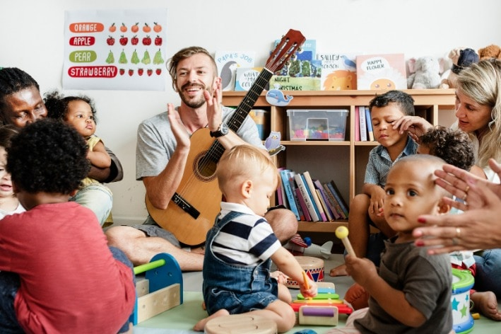 Teacher holding a guitar surrounded by a group of students.