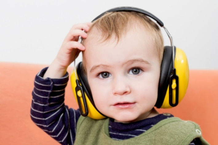 Young boy with headphones on him.