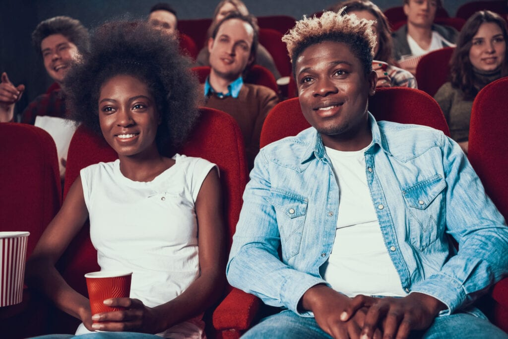 Couple with popcorn watching movie in cinema.