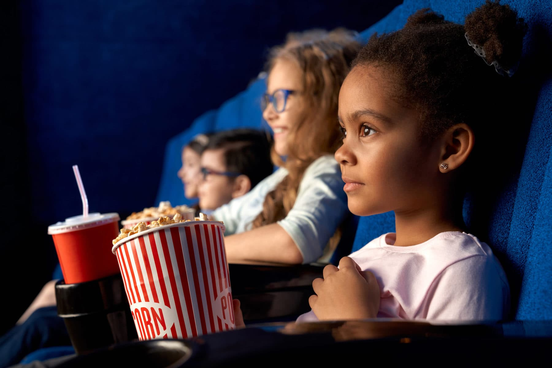 Young children sitting in movie theatre holding popcorn.