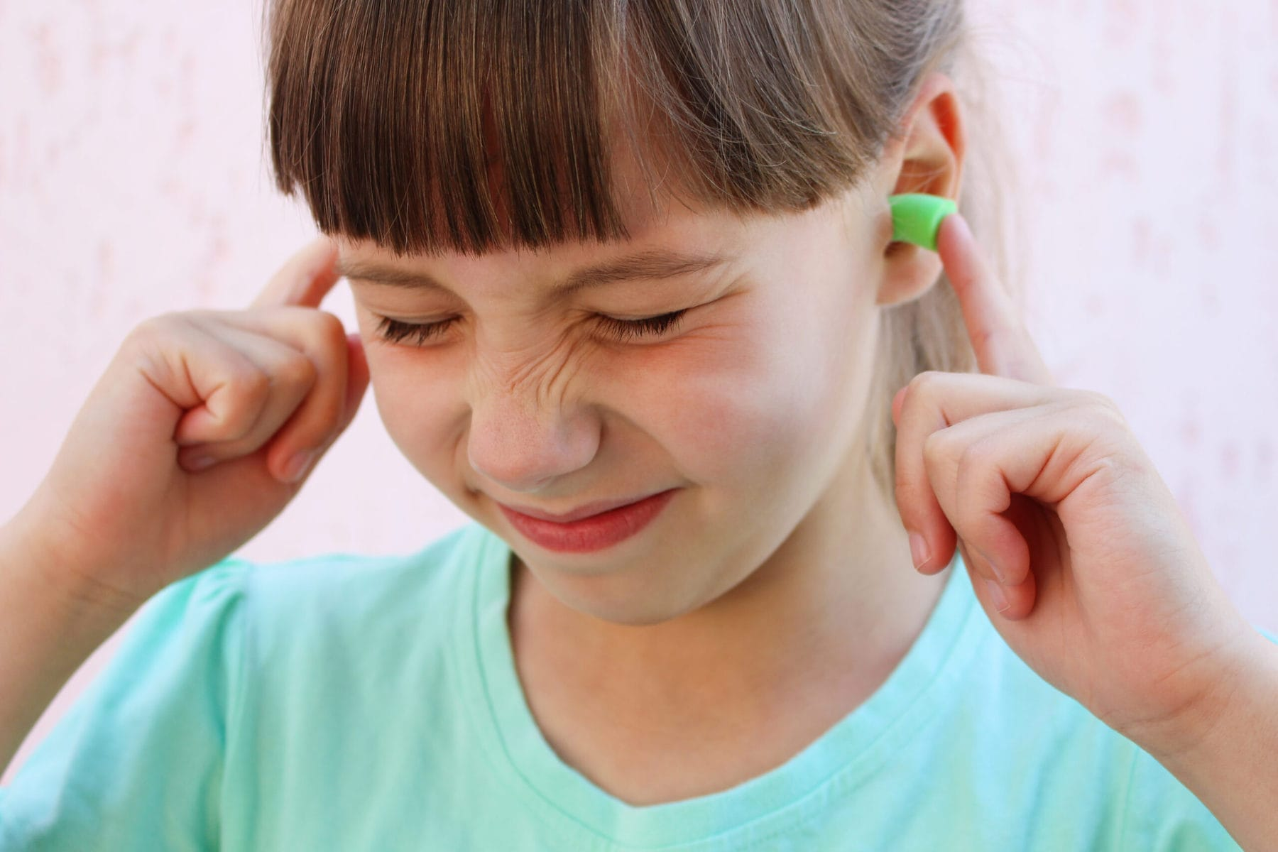 Girl with ear plugs to protect against sensory overload and noise.