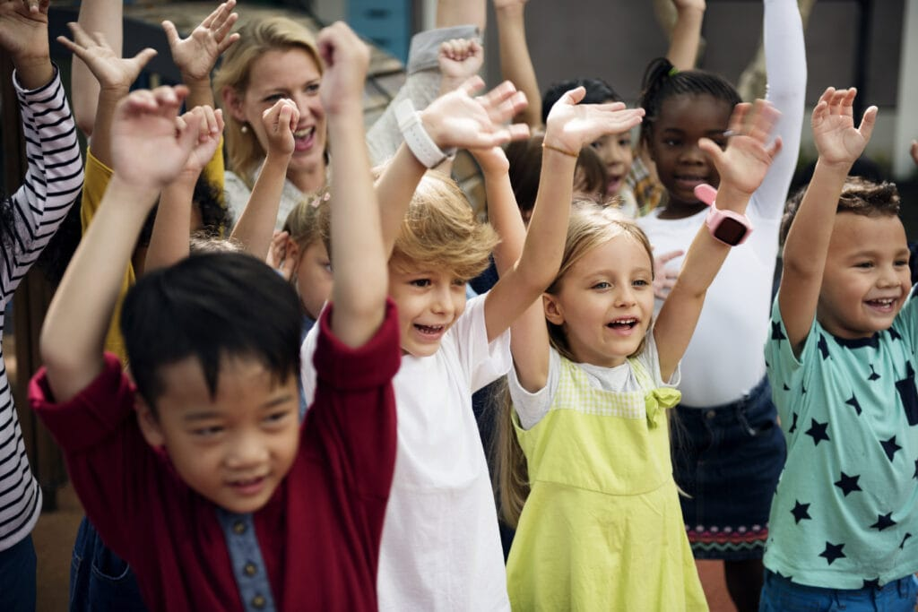 Happy kids at elementary school with their hands raised.