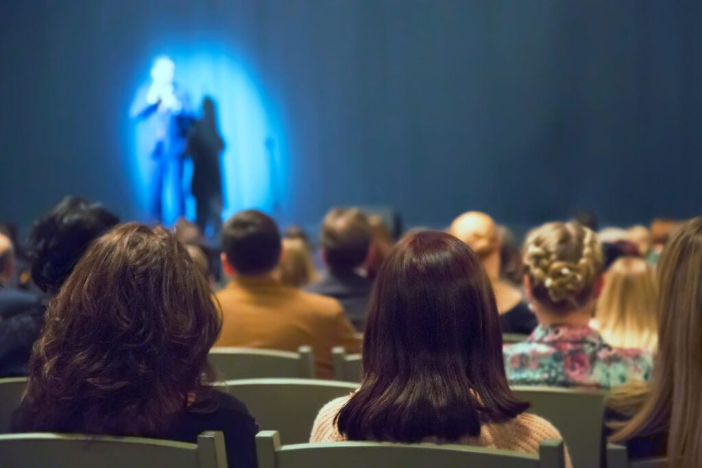 Man appears on stage in theater with many people.