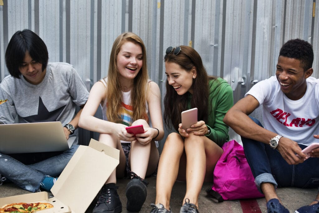 Group of students sitting on concrete floor looking at cellphones.
