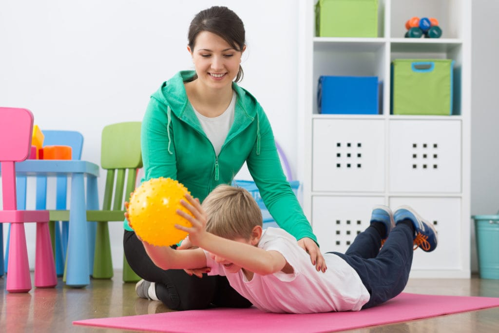 Child playing with sensory friendly ball with adult.