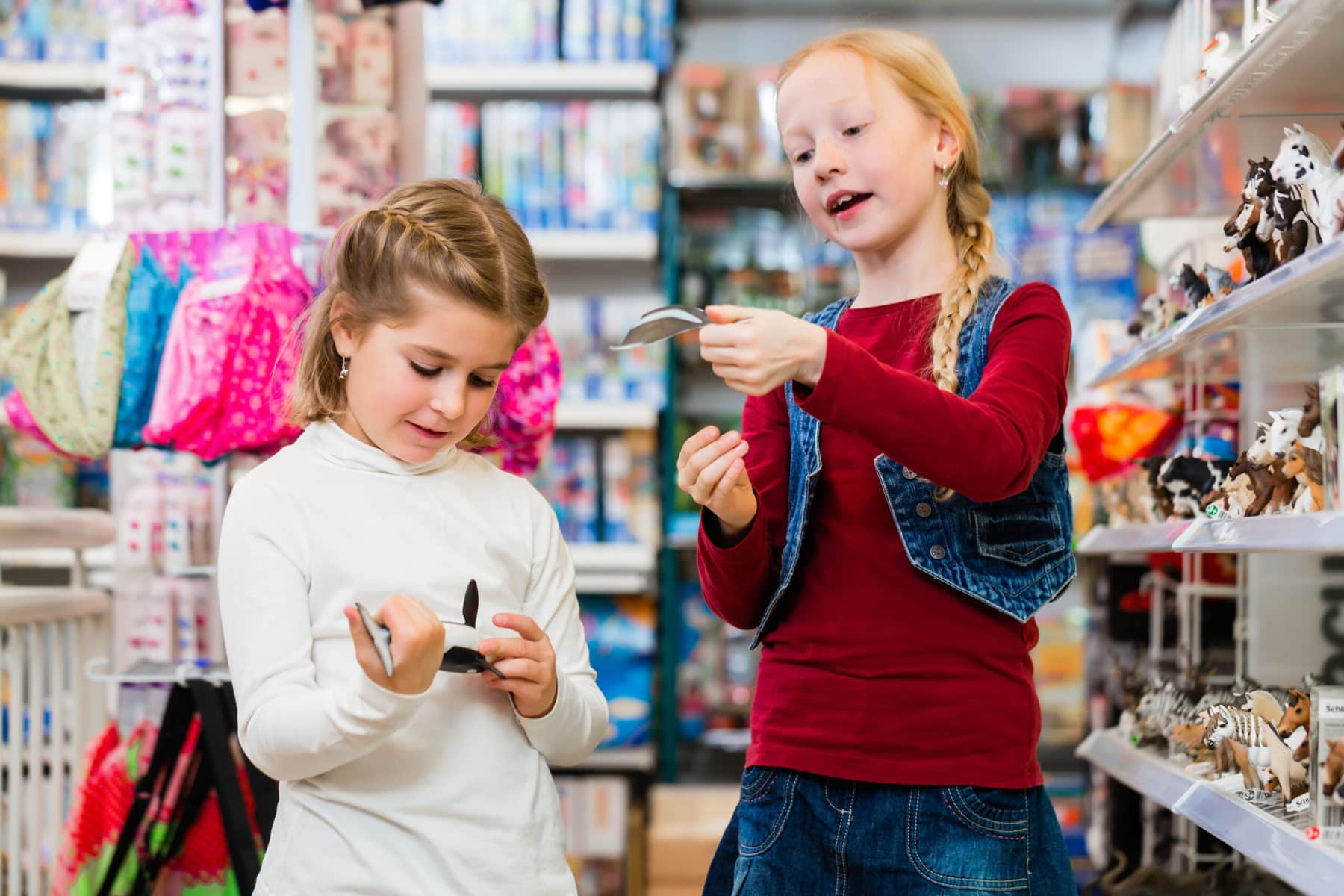 Two kids buying toys in toy store close to a shelf with figures