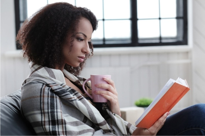 Black woman reading book holding mug.