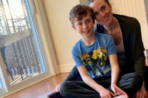 Lindsay Hall and young boy sitting on yoga mat.