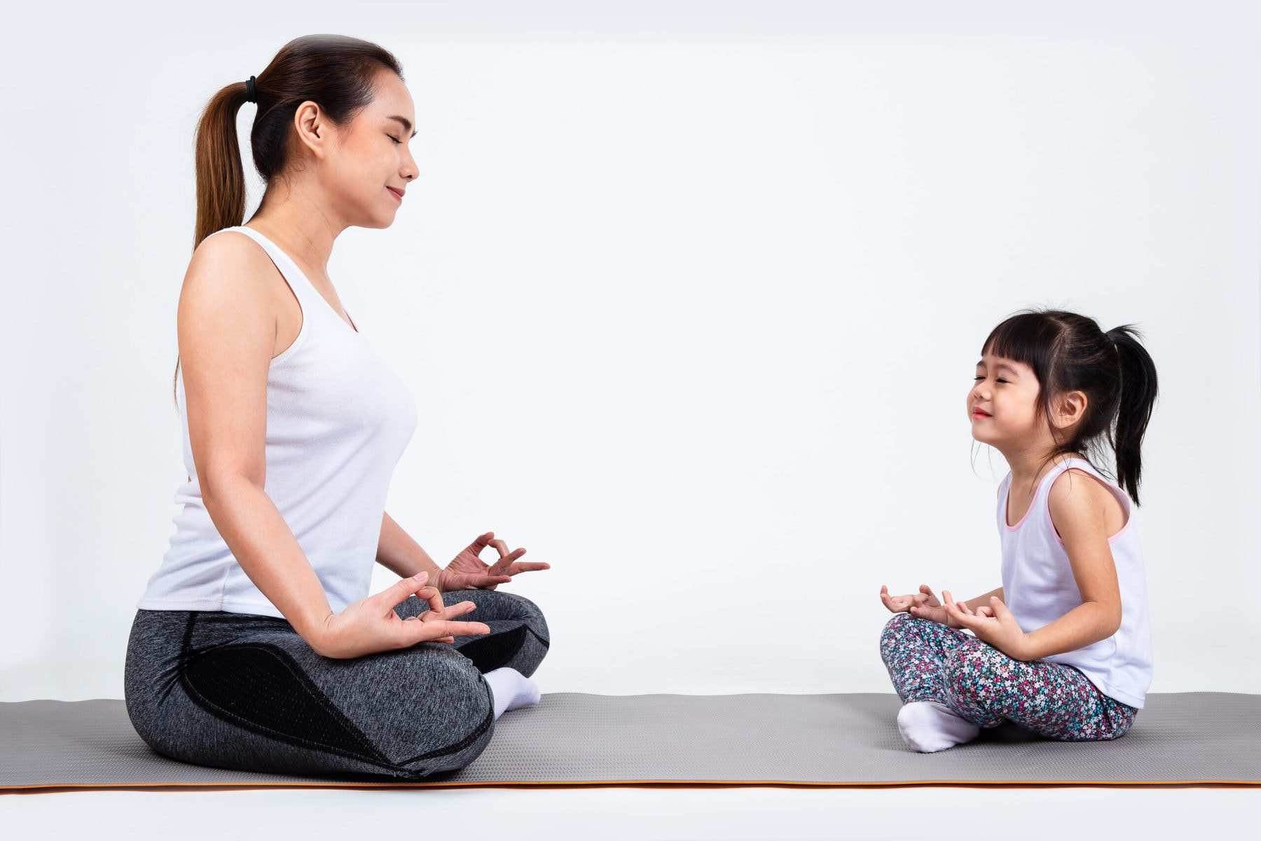 Daughter and mother sitting on yoga mat meditating.