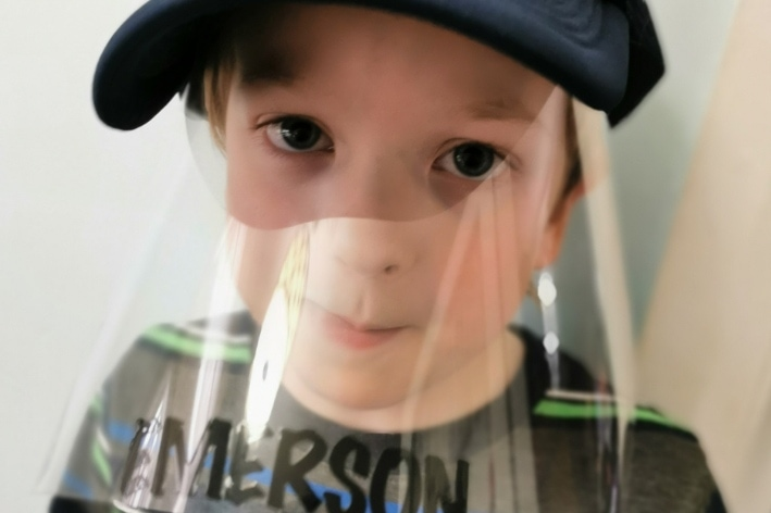 Young boy wearing home made face shield