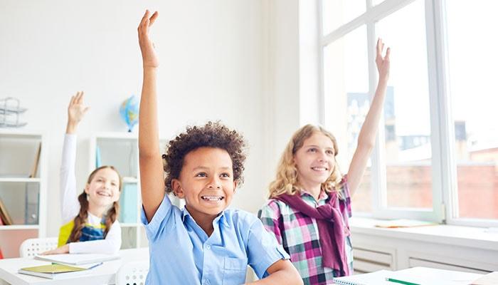 Children in classroom raising hands