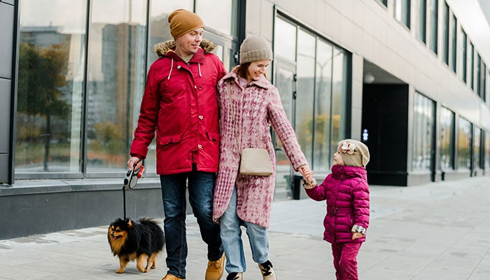 Family with young child and dog out for a walk downtown during winter
