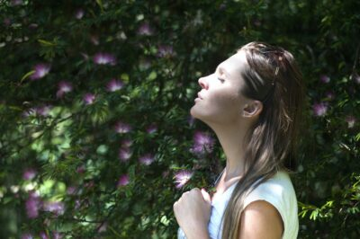 Woman with eyes closed taking a deep breath outside to help with reducing noise.