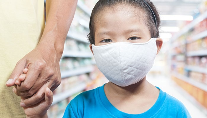 Child wearing mask holding hand of a parent in a supermarket